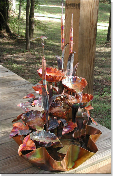 Six tiered copper waterfall with cattails.